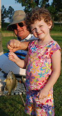 young female child holding the line with a bluegill sunfish on it